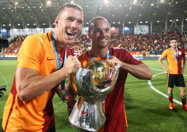 Galatasaray's Polish forward Lukas Podolski (L) and Dutch midfielder Wesley Sneijder celebrate with the trophy after winning the 2015 Turkish Super Cup final match against Bursaspor at Osmanli Stadium in Ankara