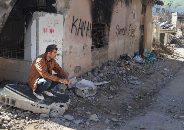 A resident of Cizre sits next to his ruined and burned house.
