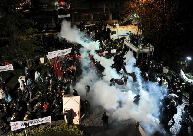 Riot police use tear gas to disperse protesting employees and supporters of Zaman newspaper at the courtyard of the newspaper's office in Istanbul, Turkey, late March 4, 2016