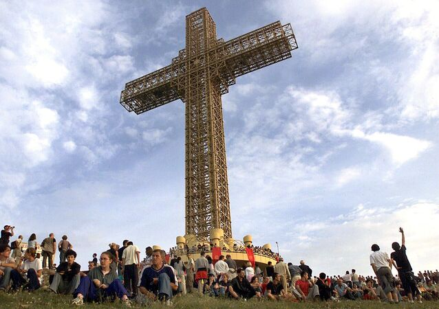 Macedonian Orthodox believers sit around a massive metal cross during its sanctification ceremony on top of Mt. Vodno, just above Macedonia's capital Skopje, on Wednesday, Aug. 28, 2002