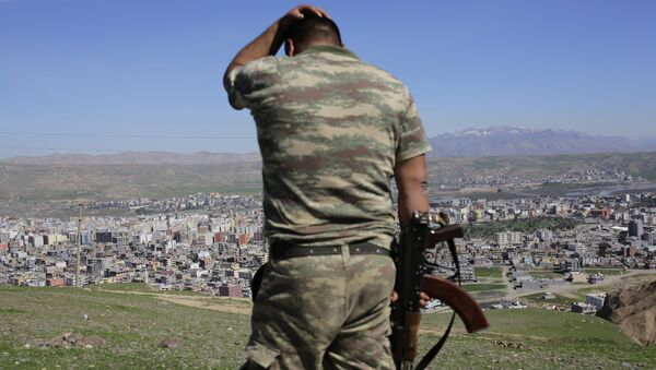 A Turkish soldier gestures while standing on the hill overlooking damaged buildings following heavy fighting between government troops and Kurdish fighters in the Kurdish town of Cizre in southeastern Turkey, which lies near the border with Syria and Iraq, on March 2, 2016 - Sputnik International