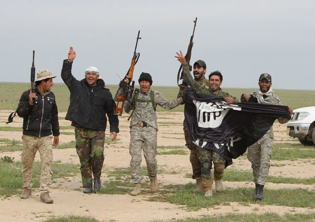 Iraqi Shiite fighters from the Popular Mobilisation units carry an Islamic State (IS) group flag on March 3, 2016, during an operation in the desert of Samarra aimed at retaking areas from IS jihadists