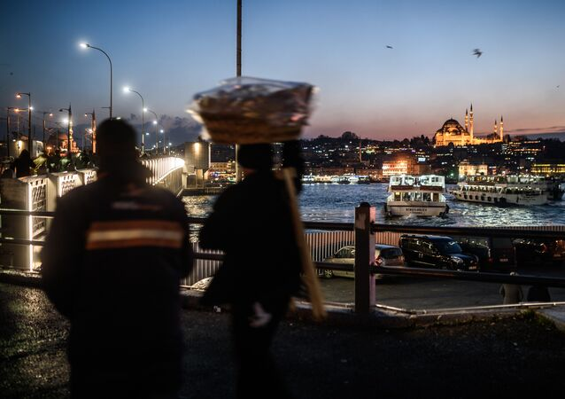 A vendor passes Galata Bridge near the illuminated Suleymaniye mosque in Istanbul on January 25, 2016