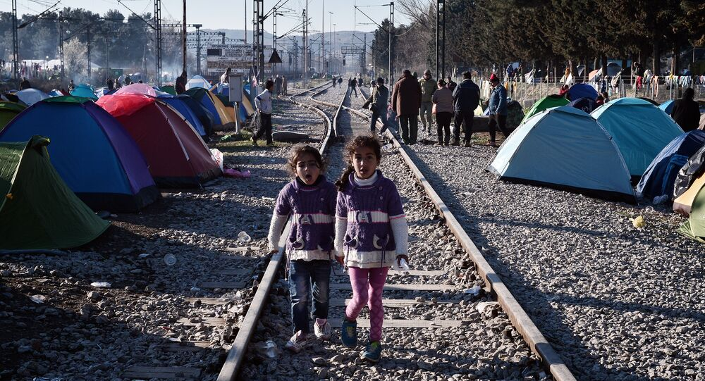 Sisters walk on railway tracks where refugees installed their tents at the makeshift camp of the Greek-Macedonian border near the Greek village of Idomeni, on March 5, 2016, where thousands of refugees and migrants wait to cross the border into Macedonia