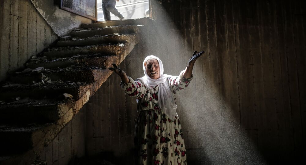 A woman reacts while walking among the ruins of damaged buildings following heavy fighting between government troops and Kurdish fighters, on March 2, 2016 in the southeastern Turkey Kurdish town of Cizre, near the border with Syria and Iraq