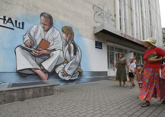 Women with children walk past graffiti showing Russian President Vladimir Putin, dressed in a Judogi and sitting next to a girl, on the front of a children's clinic in Yalta, Crimea, Wednesday, Aug. 19, 2015