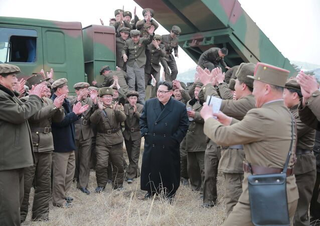 North Korean leader Kim Jong Un (C) smiles as he guides a test fire of a new multiple launch rocket system in this undated photo released by North Korea's Korean Central News Agency (KCNA) in Pyongyang March 4, 2016