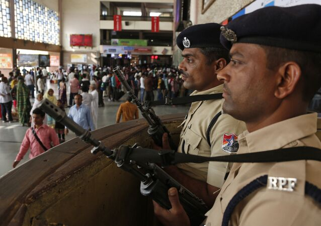 Railway policemen stand guard at a railway station following high alert in Ahmadabad, Gujarat state, India, Sunday, March 6, 2016