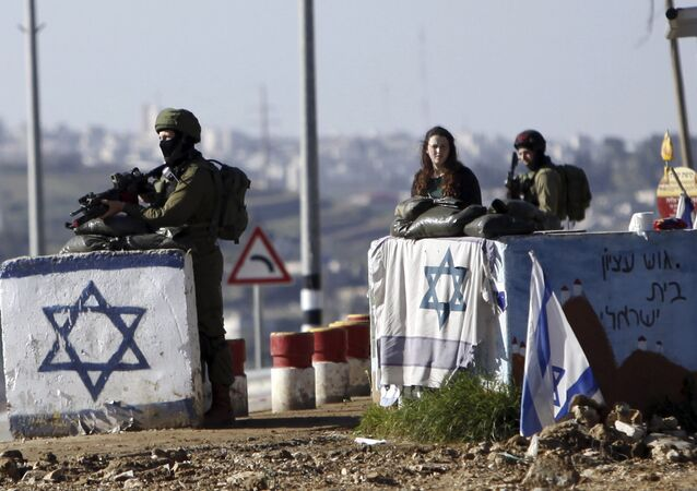 Israeli soldiers stand guard at Gush Etzion junction in the West Bank Friday, March 4, 2016