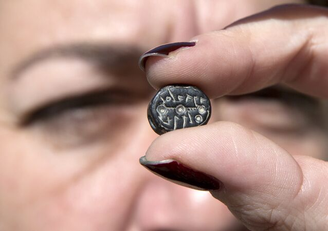 "Yana Tchekhanovets, an archaeologist with the Israeli Antiquity Authority, displays on March 7, 2016 a seal bearing the name ""Elihana bat Gael"""