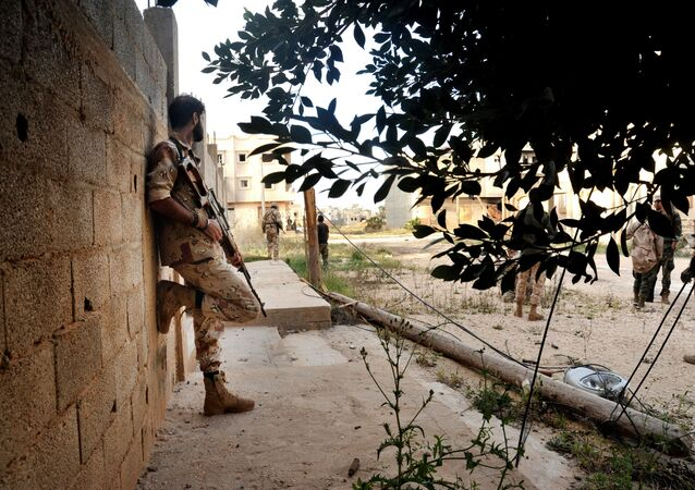 In this Monday, March 7, 2016 photo, men loyal to Libyan armed forces stand alert during clashes with Islamic State group militants west of Benghazi, Libya