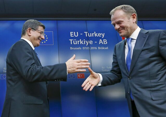 Turkish Prime Minister Ahmet Davutoglu (L) shakes hands with European Council President Donald Tusk after a news conference at the end of a EU-Turkey summit in Brussels March 8, 2016.
