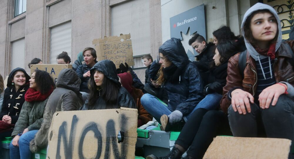 Students sit outside their high school in Paris