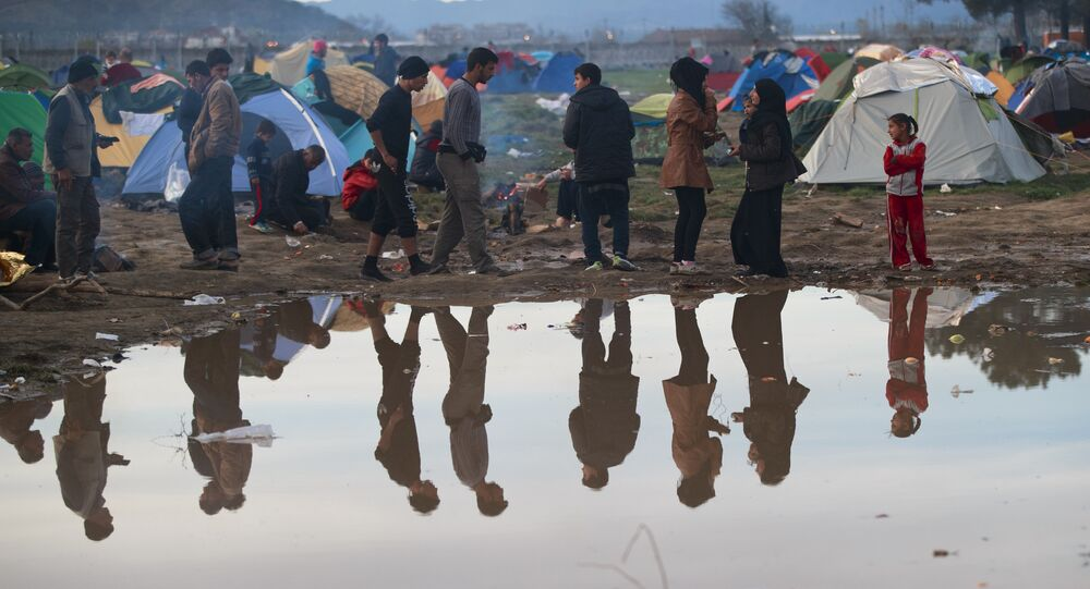 Migrants are reflected in a puddle at the northern Greek border station of Idomeni, Tuesday, March 8, 2016.