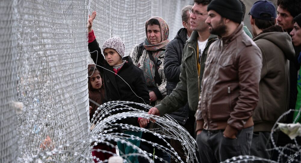 People look at the Macedonian side of the border through a fence in the makeshift camp at the Greek-Macedonian border near the Greek village of Idomeni, on March 3, 2016.