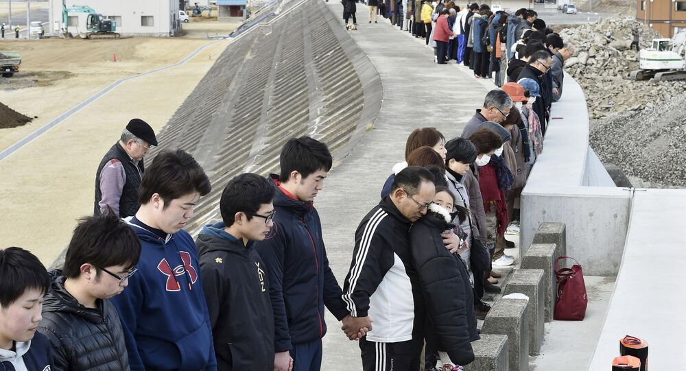People observe a moment of silence at 2:46 p.m. (0546 GMT), the time when the magnitude 9.0 earthquake struck off Japan's coast in 2011, atop of a seawall at Taro district in Miyako, Iwate prefecture, Japan, March 11, 2016, to mark the fifth-year anniversary of the March 11, 2011 earthquake and tsunami that killed thousands and set off a nuclear crisis.