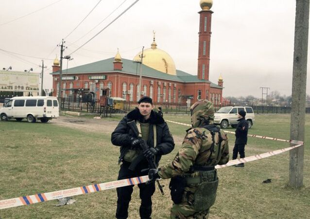 Police officers stand guard in front of a mosque after a blast in Nazran, Russia