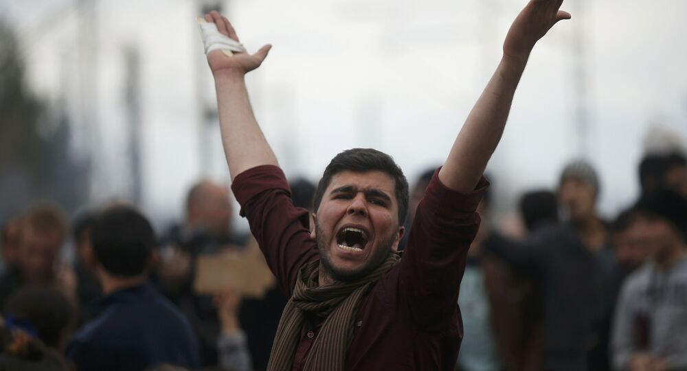 A migrant shouts slogans as he is blocking the railway track at the Greek-Macedonian border, near the village of Idomenii, Greece March 12, 2016.