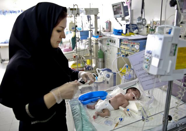 In this Monday, Dec. 30, 2013 photo, a nurse cares for a newborn baby in the Neonatal Intensive Care Unit of the Mofid Children Hospital in Tehran, Iran