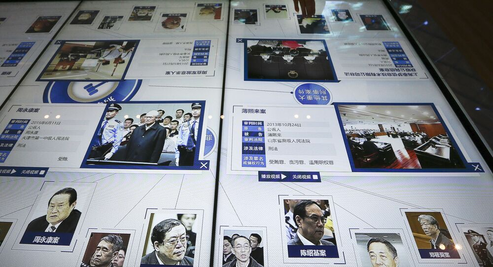 visitor, top, looks at an electronic screen displaying images and convicted corruption charges of China's fallen politicians, Bo Xilai, bottom second right, Zhou Yongkang, bottom left, and other senior officials, at the China Court Museum in Beijing, Tuesday, Jan. 12, 2016