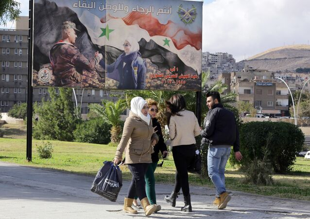 Syrians walk past a billboard bearing a national flag and a slogan which reads in Arabic You are the future and long live the country in Damascus on December 2, 2015