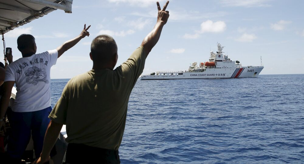 Filipino soldiers gesture at a Chinese Coast Guard vessel on the disputed Second Thomas Shoal, part of the Spratly Islands, in the South China Sea March 29, 2014