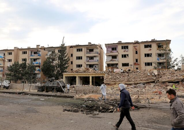 Forensic experts and plain clothes security officers inspect a police housing comlex after a car bomb and rocket attack by Kurdish militants in Nusaybin, in the southeastern province of Mardin, Turkey March 4, 2016