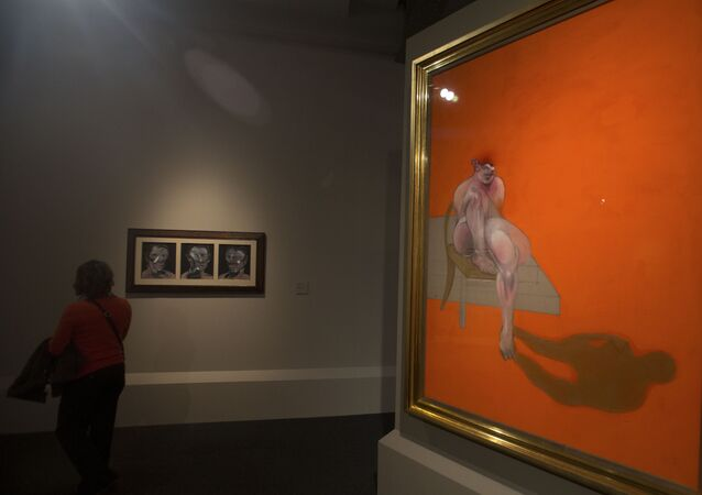 A woman looks at Francis Bacon's 3 Studies of Peter Beard left alongside part of Bacon's Triptych at the Abello Collection exhibition in Madrid, Spain, Wednesday, Nov. 5, 2014.