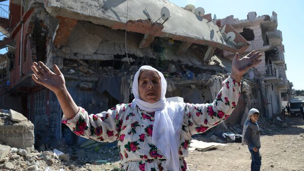 A woman reacts while walking among the rubble of damaged buildings following heavy fighting between government troops and Kurdish fighters in the Kurdish town of Cizre in southeastern Turkey, which lies near the border with Syria and Iraq, on March 2, 2016 - Sputnik International