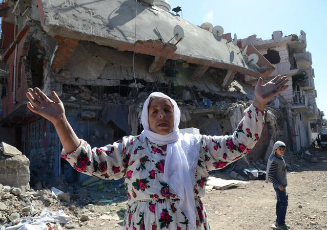 A woman reacts while walking among the rubble of damaged buildings following heavy fighting between government troops and Kurdish fighters in the Kurdish town of Cizre in southeastern Turkey, which lies near the border with Syria and Iraq, on March 2, 2016