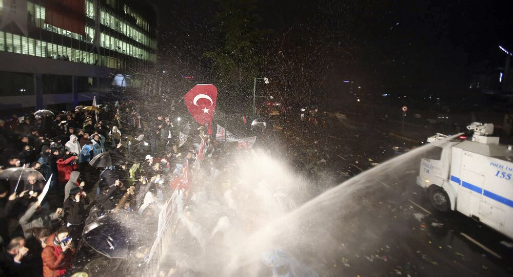 Riot police use water canon against people gathered in support of Turkey's largest-circulation newspaper Zaman at its headquarters in Istanbul, early Saturday, March 5, 2016