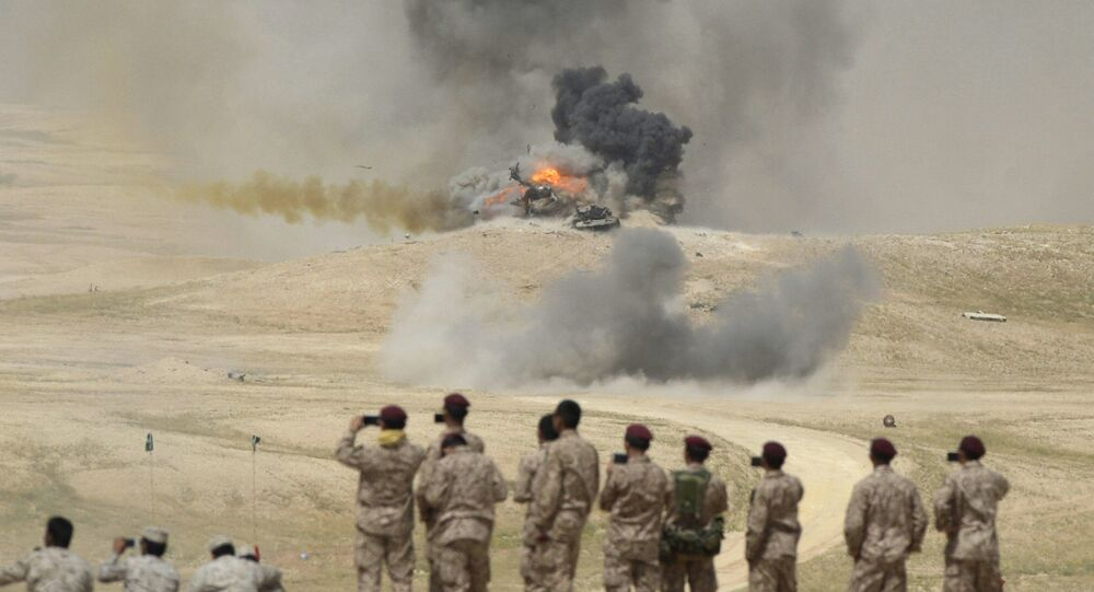 Soldiers take pictures as flame and smoke are seen following air bombardments during the Northern Thunder exercises, in Hafr Al-Batin, near Saudi Arabia's border with Iraq, March 10, 2016