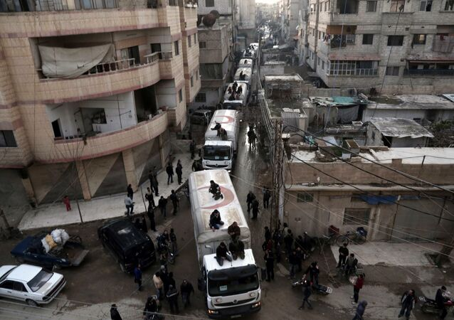 This file photo taken on February 23, 2016 shows a Red Crescent convoy carrying humanitarian aid arriveing in Kafr Batna, in the rebel-held Eastern Ghouta area, on the outskirts of the capital Damascus during an operation in cooperation with the UN to deliver aid to thousands of besieged Syrians