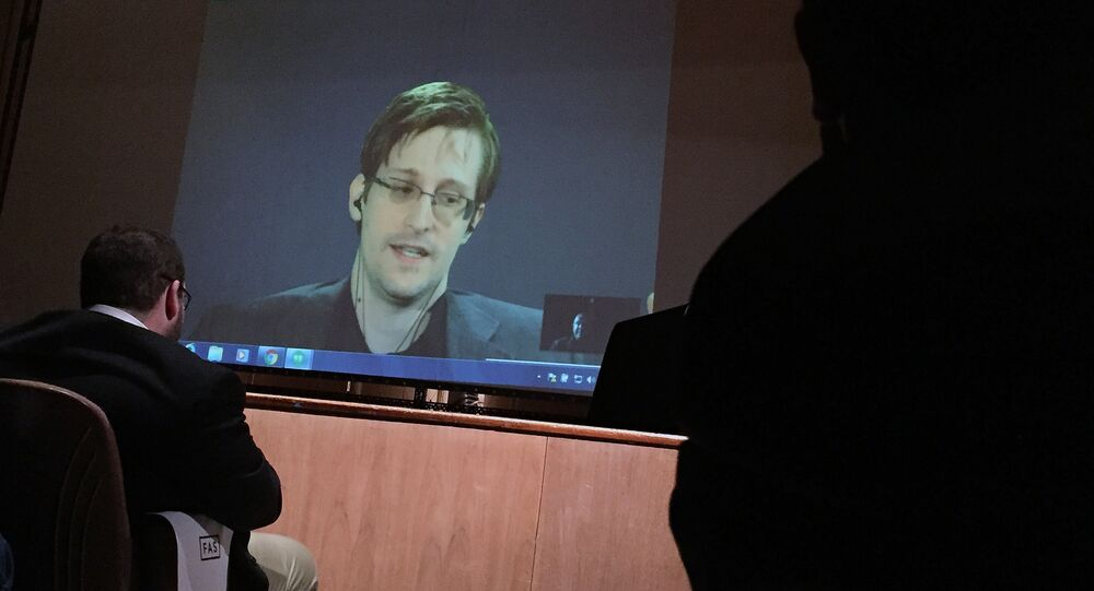 Former National Security Agency contractor Edward Snowden, center speaks via video conference to people in the Johns Hopkins University auditorium, Wednesday, Feb. 17, 2016, in Baltimore