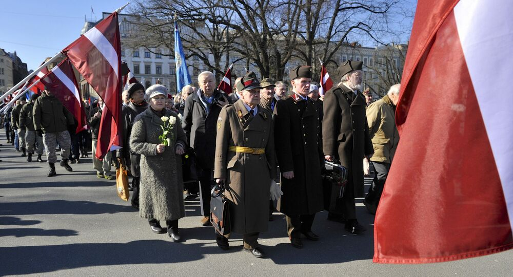 People carry flowers and Latvian flags as they march to the Freedom Monument to commemorate World War II veterans who fought in Waffen SS divisions, in Riga, Latvia, Monday, March 16, 2015