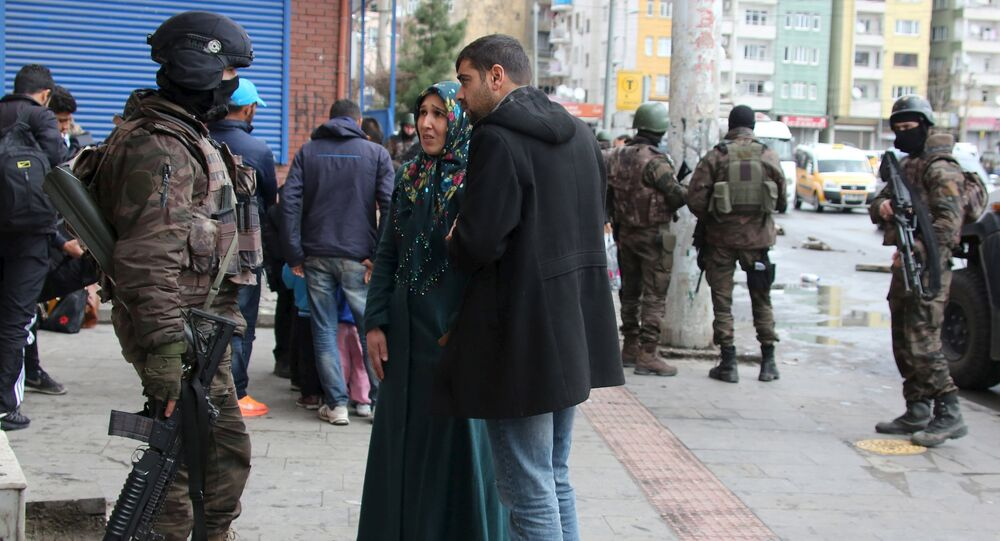 Residents talk to a member of Turkish police special forces as they flee after clashes between security forces and Kurdish militants from Baglar district, which is partially under curfew, in the Kurdish-dominated southeastern city of Diyarbakir, Turkey March 15, 2016