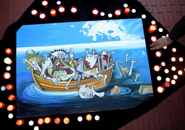A woman places a candle next to a painting, based on a Picasso painting titled Guernica, depicting the sinking of a boat carrying immigrants during a protest against the EU-Turkey migrant deal in Malaga, southern Spain, March 16, 2016.
