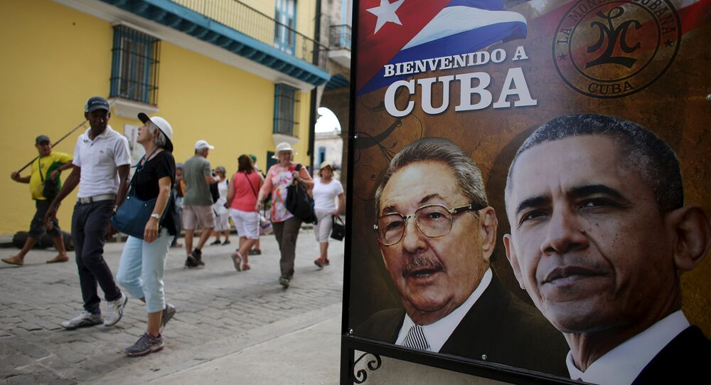 Tourists pass by images of U.S. President Barack Obama and Cuban President Raul Castro in a banner that reads Welcome to Cuba at the entrance of a restaurant in downtown Havana, March 17, 2016.