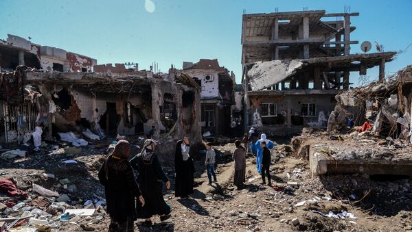 Woman walk next to ruined houses and shops on March 8, 2016 during International Women's day in Cizre district. Residents of Cizre in southeastern Turkey began returning home Wednesday after authorities partially lifted a curfew in place since December for a controversial operation against Kurdish rebels which left many homes destroyed. - Sputnik International