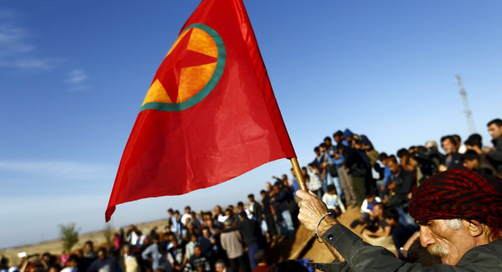 A Turkish Kurd holds a flag during the funeral of three Kurdish fighters killed during clashes in Kobani, in this October 23, 2014.