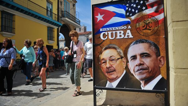 Tourists walk next to a poster of Cuban President Raul Castro and US president Barack Obama in Havana, on March 18, 2016 - Sputnik International