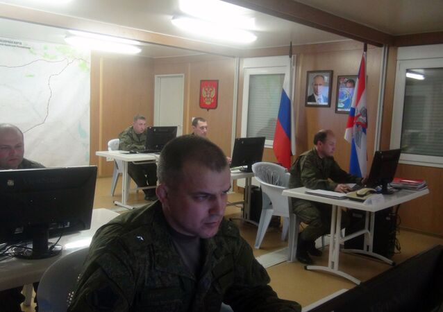Russian soldiers work behind their screens on March 17, 2016 in Russia's reconciliation center as they monitor the truce in Syria at the Hmeimim air base in the Latakia province