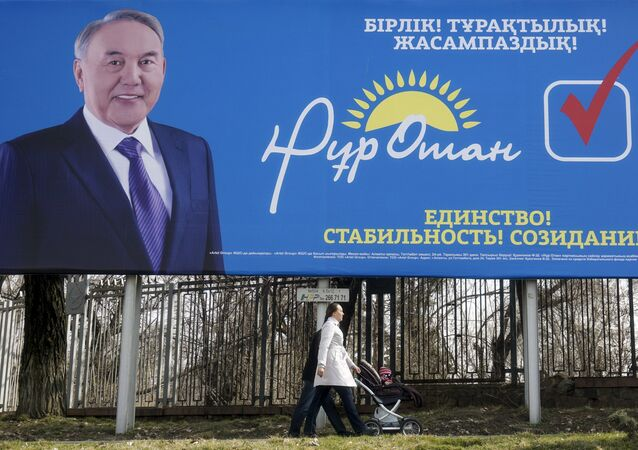 A family walks past an election poster of ruling Nur Otan party depicting Kazakhstan's President Nursultan Nazarbayev ahead of the snap parliamentary election scheduled on March 20, in Almaty, Kazakhstan, March 11, 2016