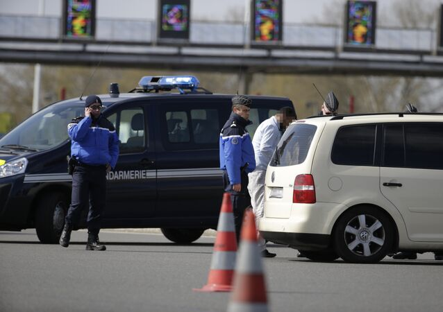 French gendarmes inspect cars at a toll in Senlis, northern France, on March 22, 2016