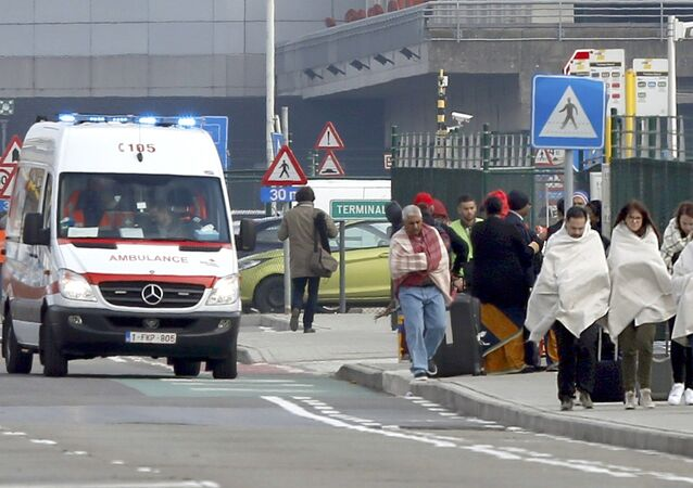 People wrapped in blankets leave the scene of explosions at Zaventem airport near Brussels, Belgium, March 22, 2016