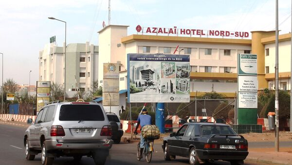 Cars drive past the Azalai Nord-Sud hotel, the site of Monday night's attack in Bamako, Mali, March 22, 2016. - Sputnik International