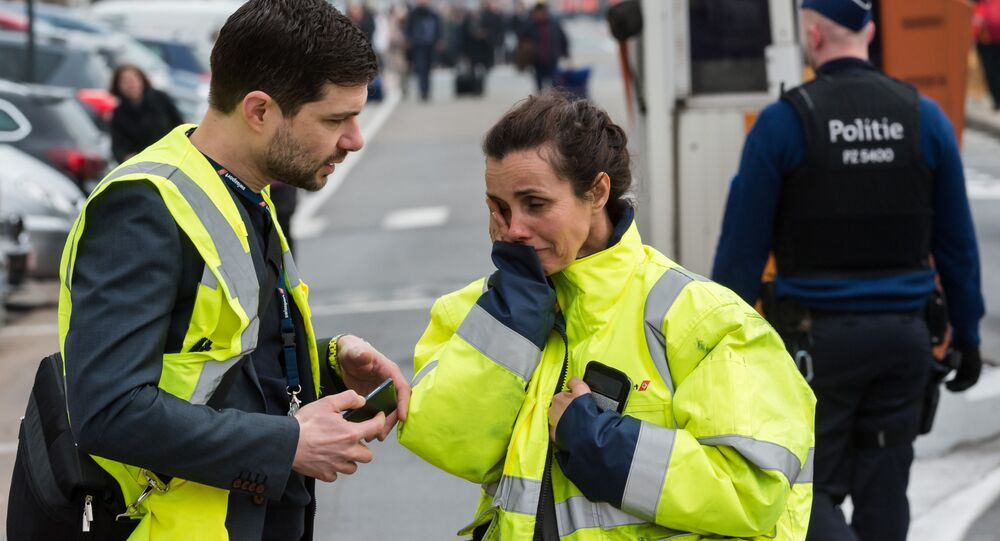 People react outside Brussels airport after explosions rocked the facility in Brussels, Belgium Tuesday March 22, 2016