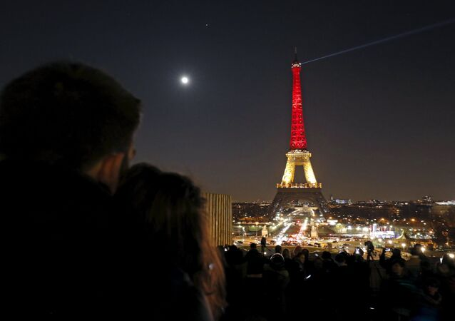 A couple looks at the Eiffel Tower lit up in the colours of the Belgian flag in tribute to the victims of today's bomb attacks in Brussels, in Paris, France, March 22, 2016