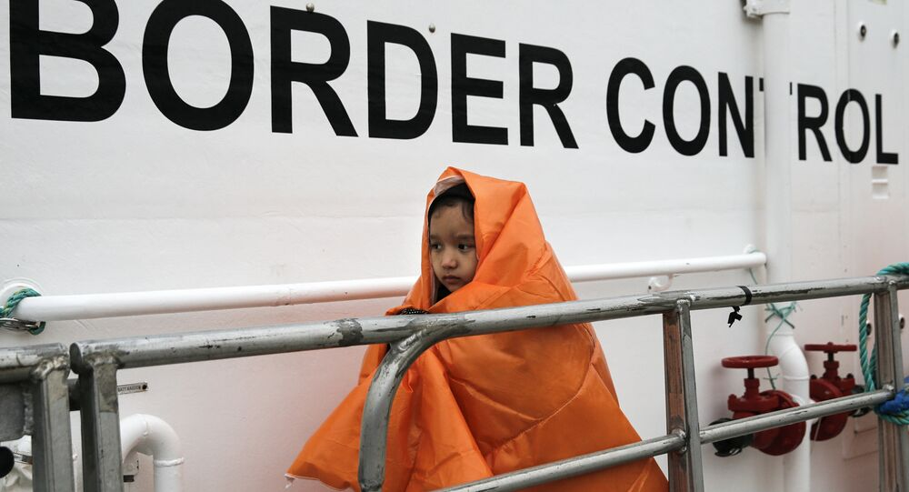 A refugee girl covered with a blanket and rescued at open sea prepares to disembark a Frontex patrol vessel at the port of Mytilene on the Lesbos island, Greece March 22, 2016.