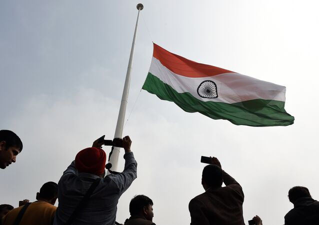 Indian residents photograph India's tallest flag as it is unveiled in Faridabad on the outskirts of New Delhi on 3 March 2015